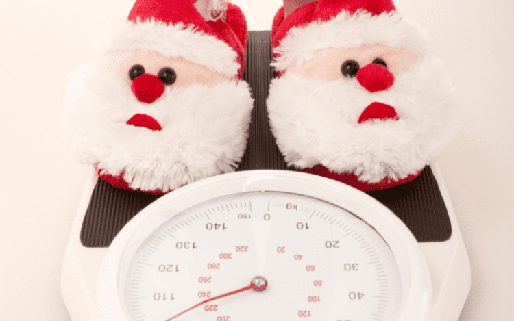 pair of santa slippers on a scale | avoid Christmas weight gain | goodMix