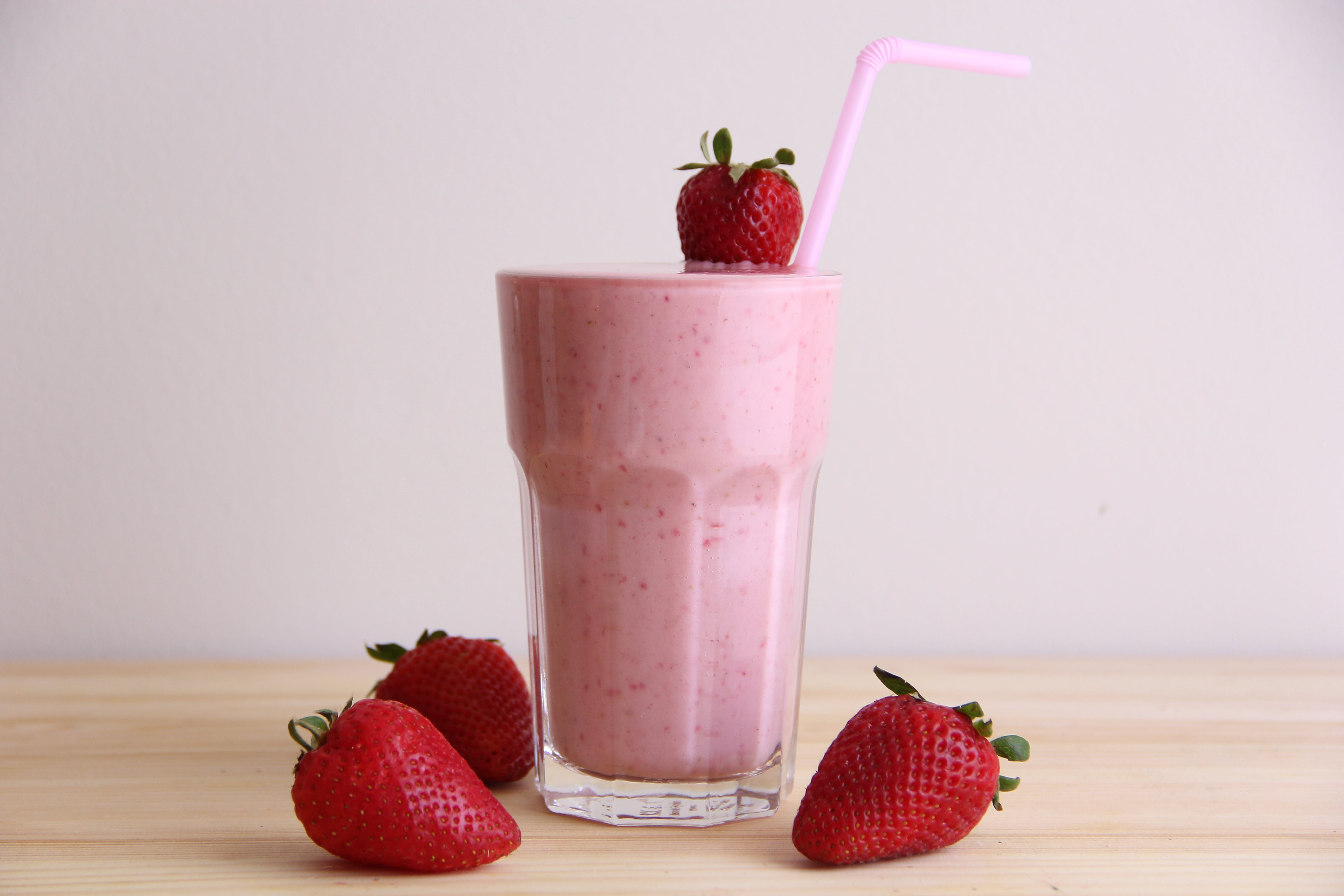 strawberry banana smoothie in a glass with whole strawberries | goodMix Superfoods