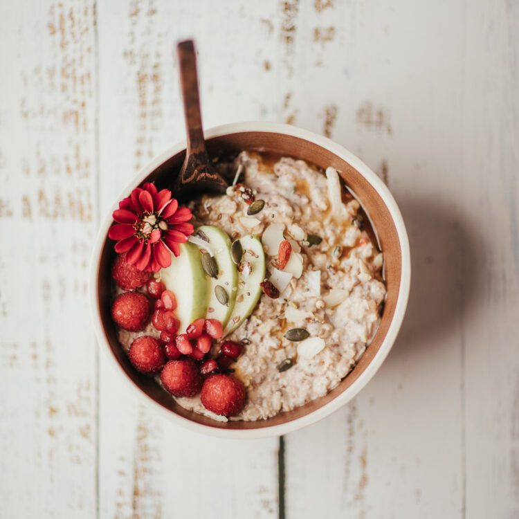 low FODMAP coconut bircher recipe in a bowl on a wooden table | goodMix